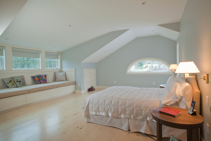 Spacious bedroom with light hardwood floors and a window seat