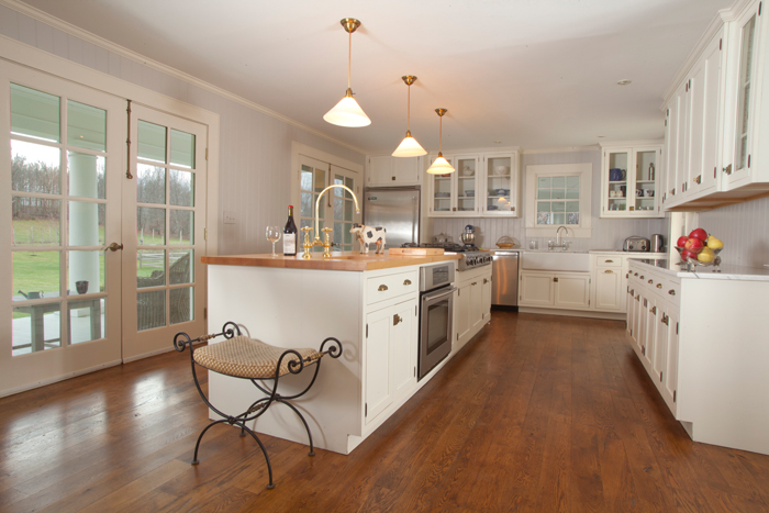 Open kichen with dark hardwood floors and white cabinets